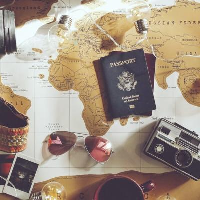 世界地図の上に広げられた海外の渡航への持ち物